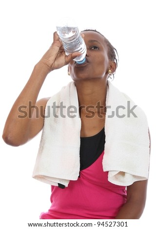 Young African woman drinking water after hard exercise session