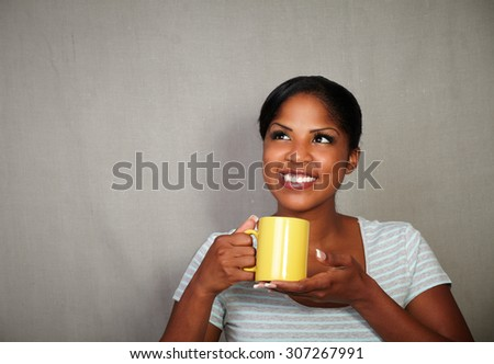 Young african woman in her 20s holding a tea cup while standing against grey background - stock photo