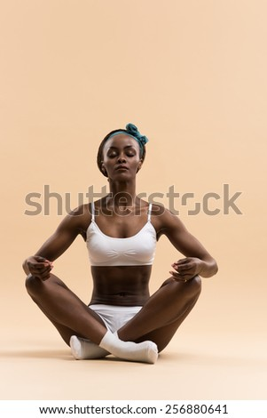 Young African woman in the lotus meditation position doing yoga - stock photo