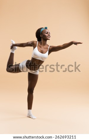 Young African woman in the stretching yoga position - stock photo