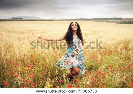 Young african woman jumping in field - stock photo