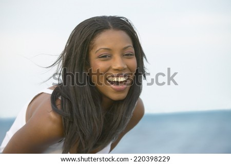 Young African woman laughing outdoors - stock photo
