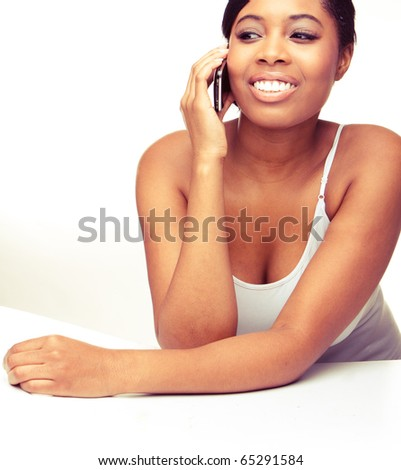 Young  African woman laughing while on mobile phone on plain white