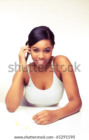 Young  African woman laughing while on mobile phone on plain white looking in the front - stock photo