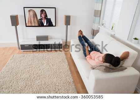 Young African Woman Lying On Sofa Watching Television At Home - stock photo