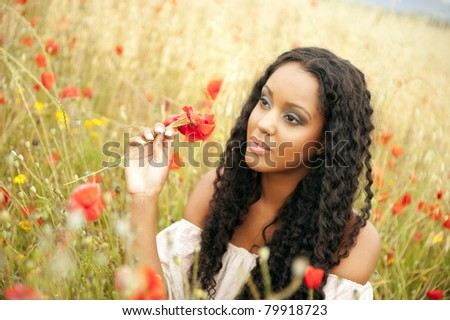 Young african woman picking flowers - stock photo
