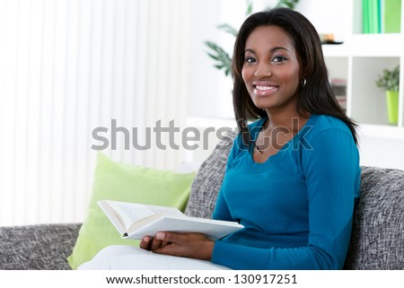 Young African woman reading book in living room - stock photo