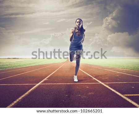 Young african woman running on a running track - stock photo