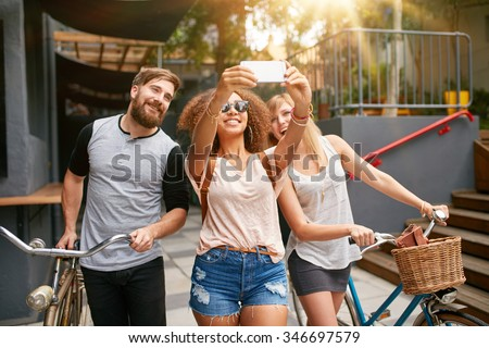 Young african woman taking a self portrait with her friends. African woman taking selfie with mobile phone. Young friends with bikes having fun on city street. - stock photo