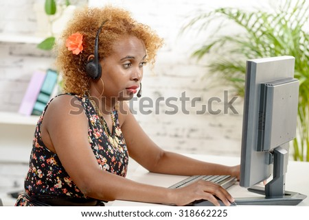 young African woman with a headset and computer - stock photo