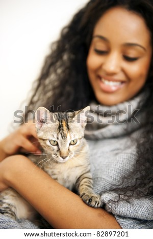 Young african woman with cat indoors - stock photo