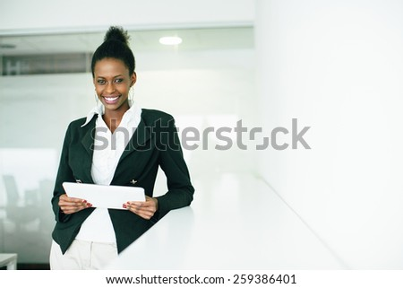 Young african woman with tablet in the office - stock photo