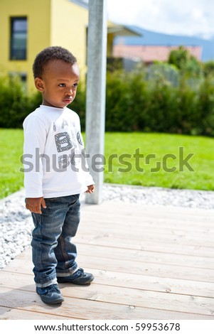 Young afro american baby playing around in the garden. - stock photo