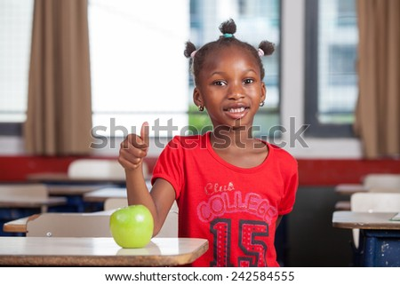 Young afro american black girl at classroom desk smiling with a green apple. - stock photo