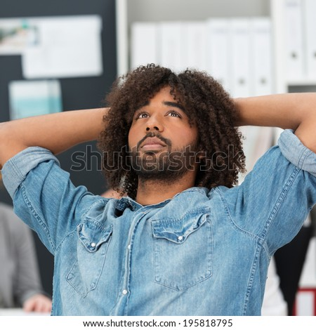 Young Afro-American businessman thinking reclining back in his chair with his hands clasped behind his head as he tries to find imaginative ideas for a project - stock photo