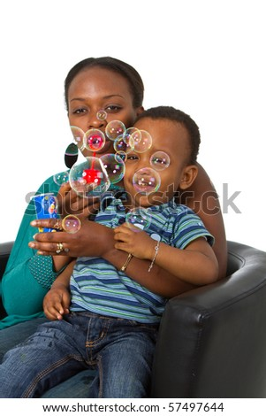 Young afro american family playing around with bubbles. Fresh young image. - stock photo