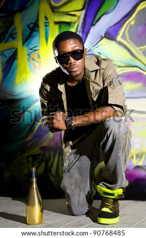 young afro-american man sitting in front of colorful graffiti wall - stock photo