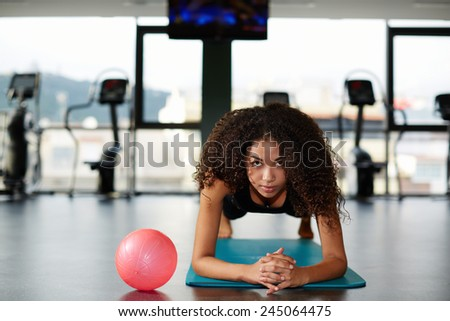 Young afro american woman leaning on her elbows doing legs exercise at gym - stock photo