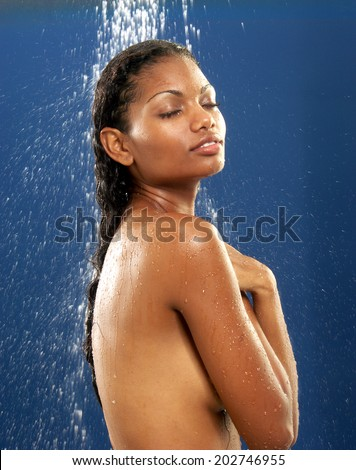 Young afro american woman taking shower. - stock photo