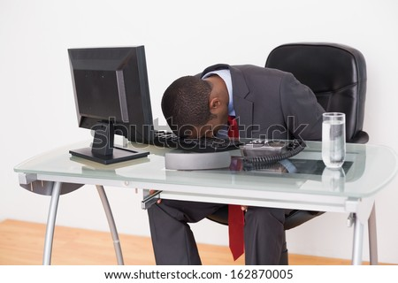 Young Afro businessman resting head on keyboard in the office - stock photo