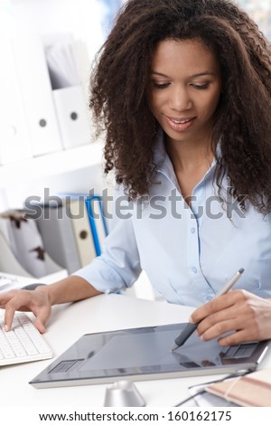 Young afro designer using drawing table, sitting at desk. - stock photo