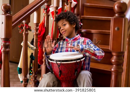 Young afro drummer on stairs. Friendly afro child with drum. Playing djembe like a pro. Free Christmas concert. - stock photo