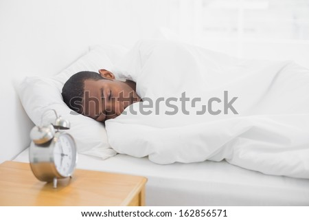 Young Afro man sleeping in bed with alarm clock in foreground at bedroom - stock photo
