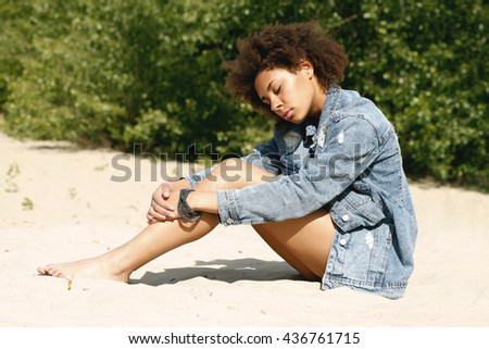 Young afro woman on the beach.