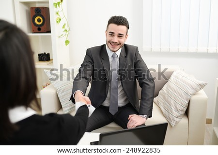 young agent salesman shaking hands at a customer home - stock photo