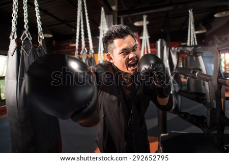 young aggressive businessman training shadow boxing at gym with gloves throwing vicious punch in angry rage face expression. fighting business concept. - stock photo