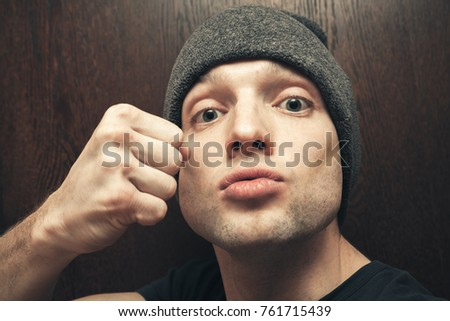 Young aggressive Caucasian man in gray hat shows fist. Closeup studio face portrait, selective focus