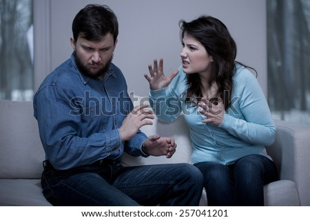 Young aggressive woman and her afraid husband - stock photo