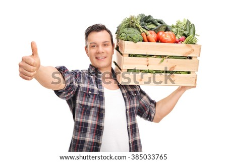 Young agricultural worker carrying a crate full of vegetables and giving a thumb up isolated on white background - stock photo