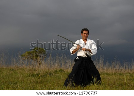 young aikido man with a sword outdoors - stock photo