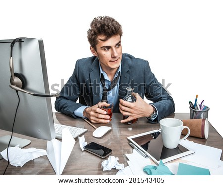 Young alcoholic business man drinking whiskey sitting drunk at office with computer holding glass looking depressed wearing loose tie in alcohol addiction problem concept - stock photo