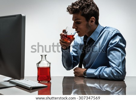 Young alcoholic man drinking whiskey sitting drunk at office with computer / photo of businessman addicted to alcohol at the workplace, depression and crisis concept - stock photo