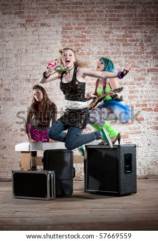 Young all girl punk rock band performs in a warehouse - stock photo