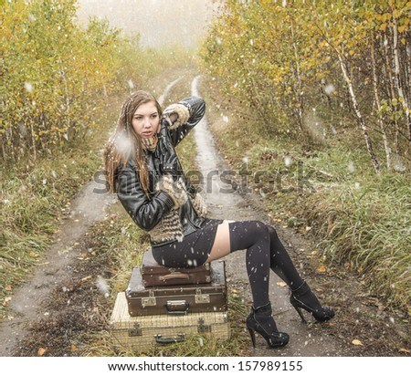 Young alone slim girl in a black leather jacket with fur collar sitting on the road in a forest in an old retro suitcase  on snowy background of the autumn snowfall  - stock photo