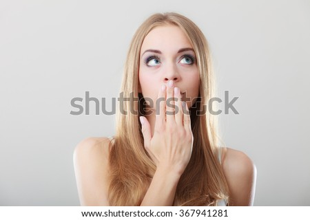 Young amazed woman covering her mouth with hand on gray