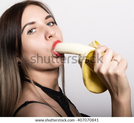 Young amazed woman in lacy lingerie holding a banana, she is going to eat a banana. she sucks a banana. - stock photo