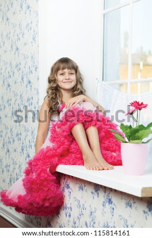 Young amazing joyful girl teenager dressed luxuriant wavy skirt with frill sitting with outstretched legs on white windowsill inside room near fresh natural flower in flowerpot - stock photo