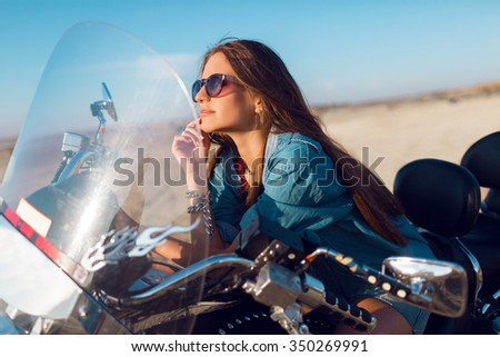 Young amazing sexy woman  sitting on  motorbike on the beach, wearing stylish crop top , shirts, have perfect fit slim tamed body and long hairs. Outdoor lifestyle   portrait. - stock photo