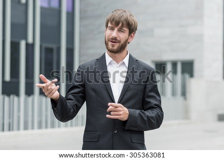 Young ambitious businessman is showing something outside company - stock photo