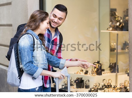 Young american adults looking at shopwindows with luxury  watches - stock photo