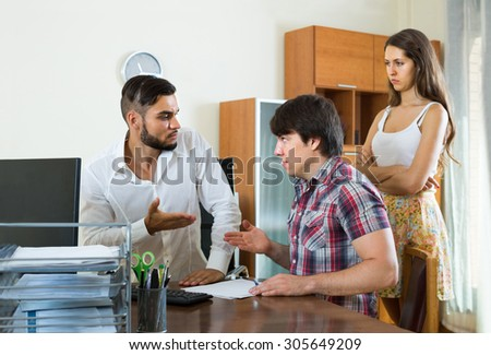Young american  boss and merried couple talking with grave countenances in the office - stock photo
