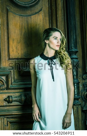 Young American Business Woman with long curly blonde hair in New York, wearing sleeveless white dress with black collar, standing by vintage style office door way, looking away. Color filtered effect
