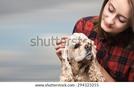Young american cocker spaniel and beautiful woman on blurred cloudy sky background with copy-space