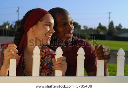 Young American couple holding on tight to a white picket fence in anticipation of all the wonderful things this life has to offer.  An upbeat, optimistic and hopeful image. - stock photo