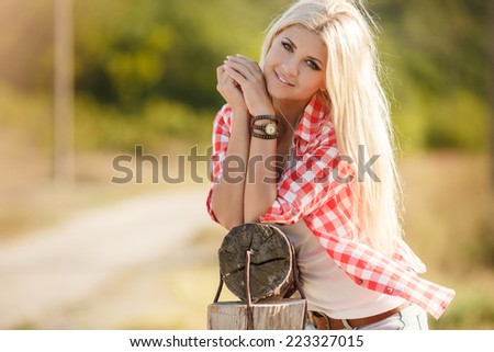 Young american cowgirl woman portrait outdoors. Beautiful natural woman saying hello looking at camera.  girl in her twenties outdoor in nature. - stock photo