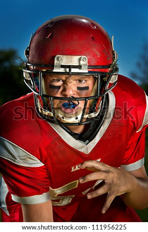 Young American football player in the ready stance. - stock photo